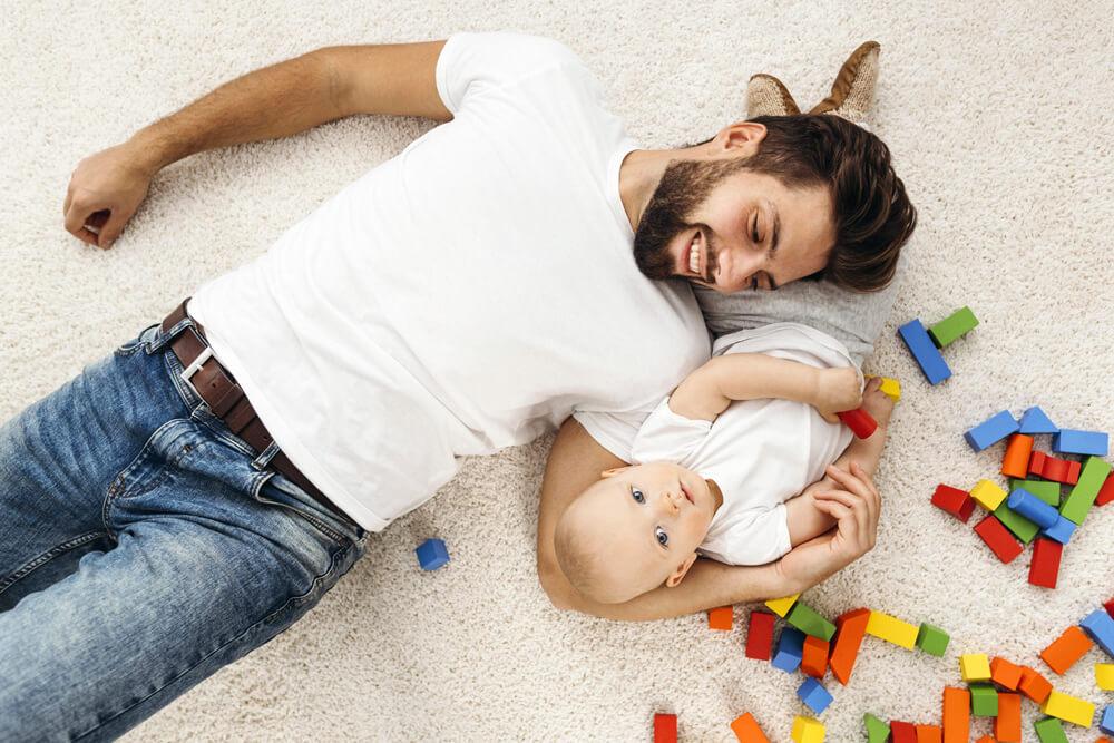 Padre tumbado en la alfombra abrazando a su hijo pequeño.