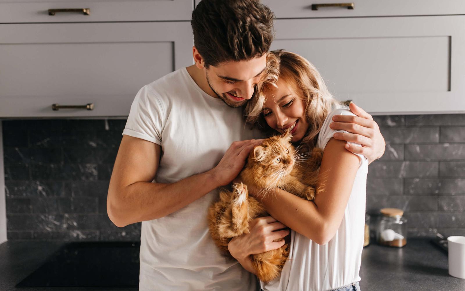 Joven pareja abrazando a un gato.