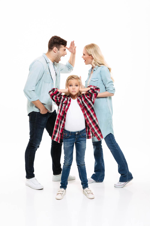 Padres discutiendo mientras la hija se tapa los oídos.