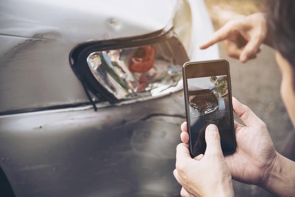 Hombre sacando una foto con el móvil a un coche averiado durante el atestado