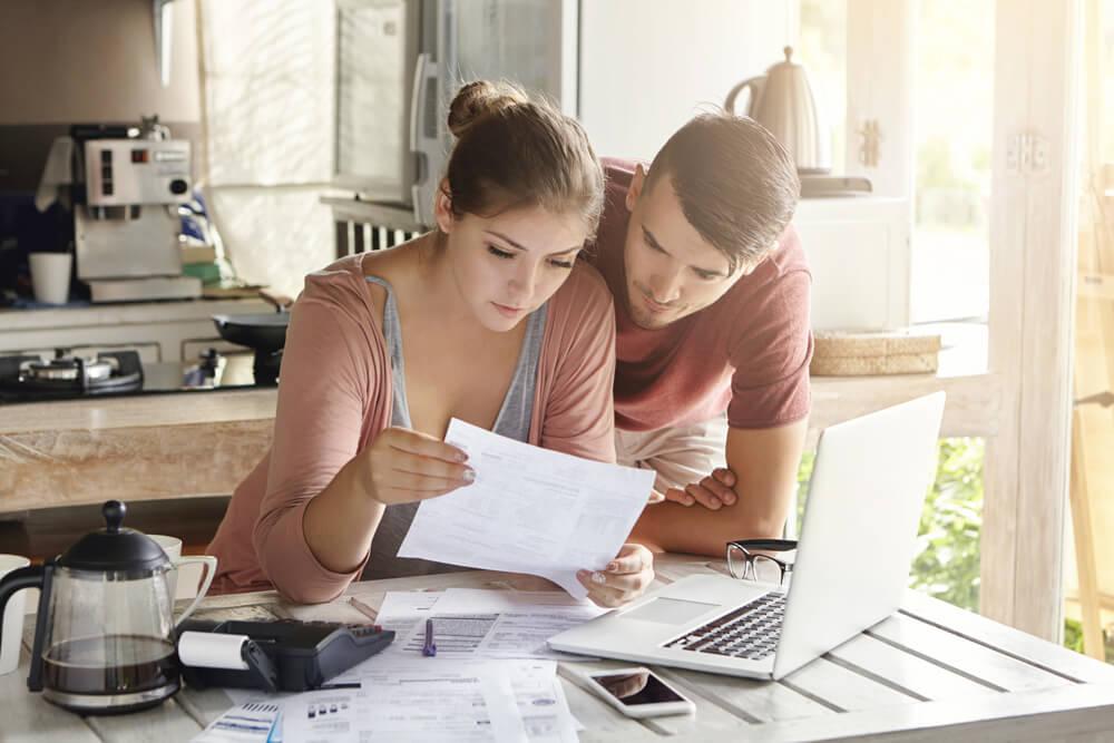 Joven pareja hace cálculos sobre los impuestos de la herencia.