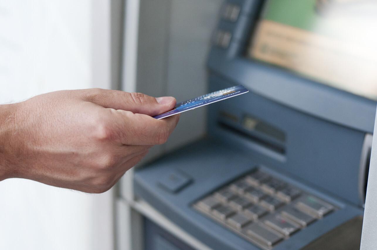 Un hombre sostiene una tarjeta de crédito delante de un cajero